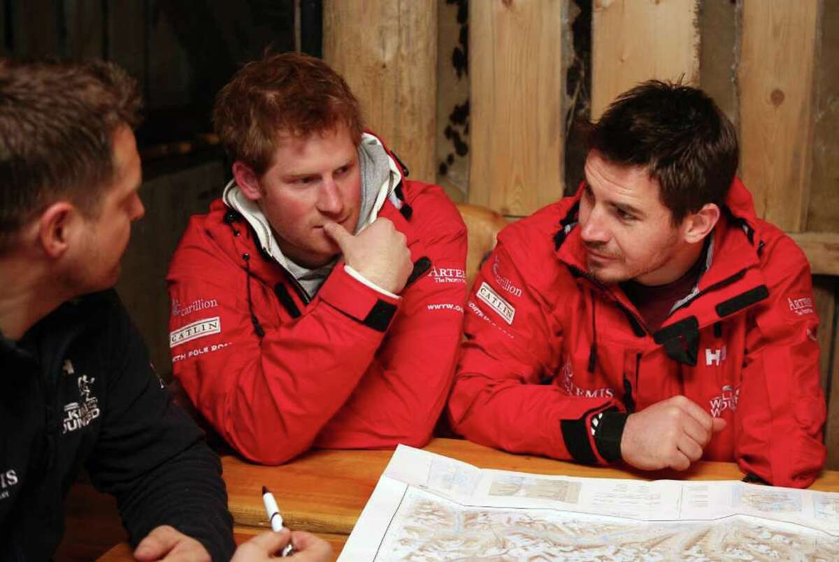SPITSBERGEN, NORWAY - MARCH 29: Prince Harry looks at some maps with team leader Inge Solheim (left) and Jaco Van Gass (right) as he joins the Walking with the Wounded team on the island of Spitsbergen, which is situated between the Norwegian mainland and the North Pole, for their last days of packing before setting off to walk to the North Pole on March 29, 2011 in Spitsbergen, Norway. (Photo by David Cheskin/WPA Pool/Getty Images) *** Local Caption *** Jaco Van Gass;Inge Solheim;Prince Harry
