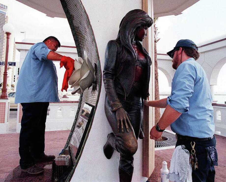 Bert Vargas, left,  and John Allen, right,  work to clean up the Selena Memorial in Corpus Christi, Texas,  The two, who work for the city parks department, are remove inscriptions  of visitors who have left their mark on the memorial.  According to Vargas, the memorial is cleaned every three to four days due to the inscriptions. Photo: THOMAS BUTLER, AP / CALLER-TIMES