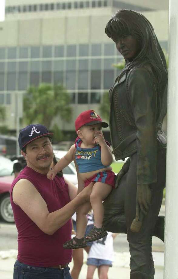 Ernesto Ipina holds up his year-old son, Brian, at the statue of Selena, the Corpus Christi native Tejano singer on Friday,  the fifth anniversary of her death. Many of her fans visited the statue, located on the Peoples Street T-head, to honor her memory. EXPRESS-NEWS PHOTO BY BILLY CALZADA Photo: BILLY CALZADA, SAN ANTONIO EXPRESS-NEWS / SAN ANTONIO EXPRESS-NEWS