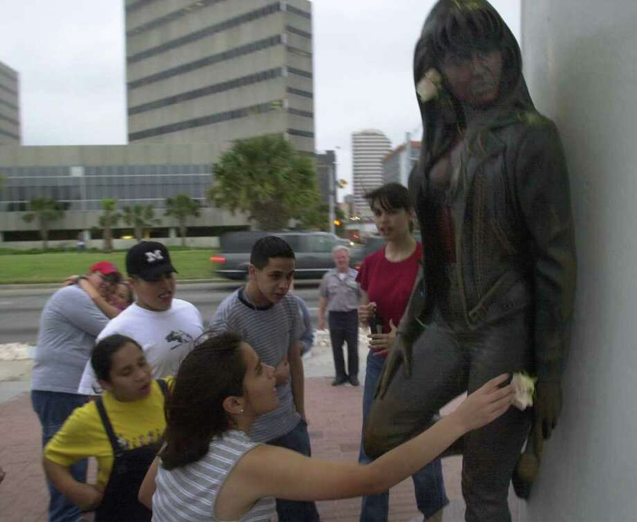 Laura Sifuentes, 16, a high-school student from Eagle Pass, touches the statue of Selena, the Corpus Christi native Tejano singer on Friday,  the fifth anniversary of her death. Many of her fans visited the statue, located on the Corpus Christi Peoples Street T-head, to honor her memory. EXPRESS-NEWS PHOTO BY BILLY CALZADA Photo: BILLY CALZADA, SAN ANTONIO EXPRESS-NEWS / SAN ANTONIO EXPRESS-NEWS