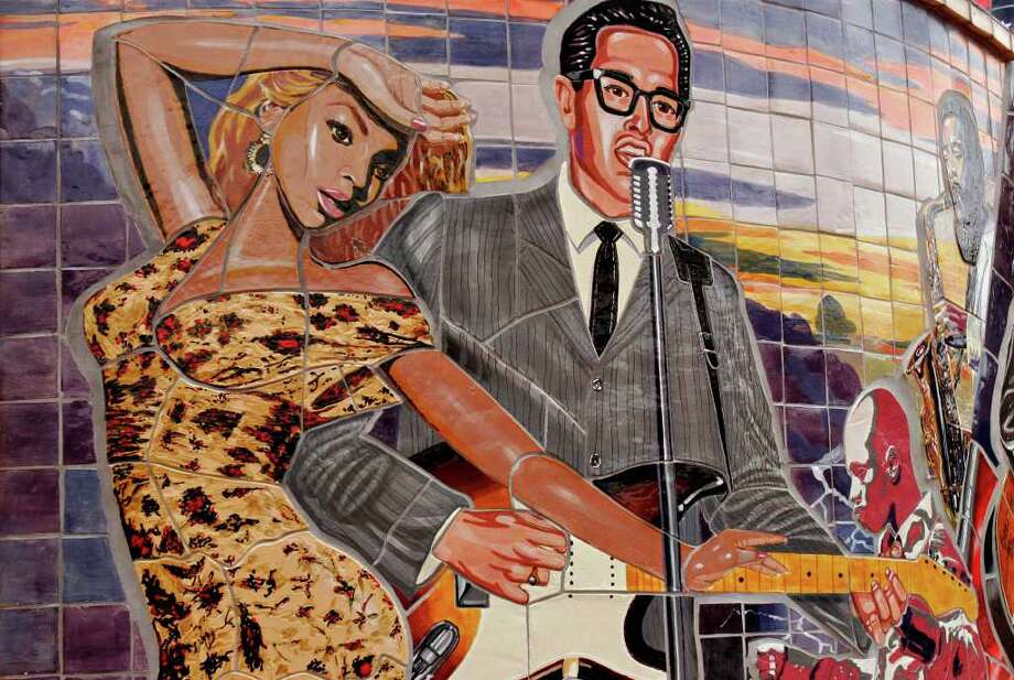 "A mural honoring Texas born musicians Buddy Holly and Beyonce is at the entrance to Sunset Station, Friday, January 12, 2007. It was  created by artist Gary V. Lett, two assistants and 20 students from an art program at Ella Austin community Center created a mural. The students, from 7 and half to 15 years of age, were part of the ""Artist in the Making"" program at the center. The 24 by 24 foot semi-circle mural features Willie Nelson, Don Santiago, Sr., Blind Lemon Jefferson, Selena, Buddy Holly, Kirk Franklin, and Lydia Mendoza. The 18-month project was unveiled Dec. 14, 2005. Nicole Fruge/ San Antonio Express-News Photo: NICOLE FRUGE, SAN ANTONIO EXPRESS-NEWS / SAN ANTONIO EXPRESS-NEWS"
