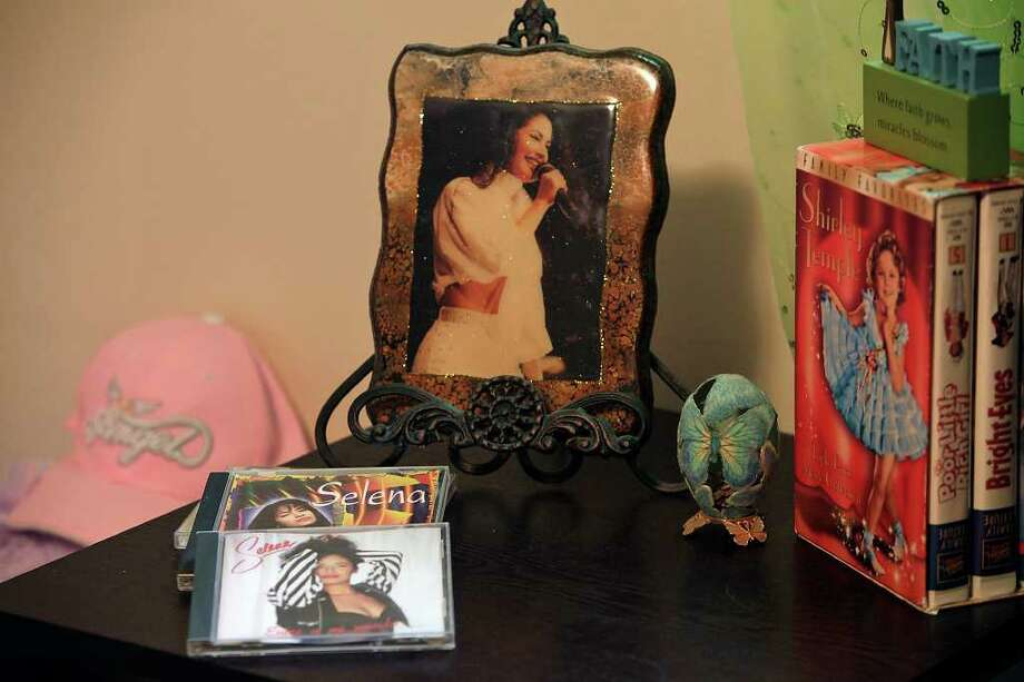 METRO -- A portrait of Selena Quintanilla sits on a table near videos of Shirley Temple at the home of Selena Aguilar, 14, in Universal City, Wednesday, March 24, 2010. She was named after Quintanilla, a popular Tejano music star, who was murdered by Yolanda Saldivar at a hotel in Corpus Christi on March 31, 1995. JERRY LARA/glara@express-news.net Photo: JERRY LARA, San Antonio Express-News / glara@express-news.net