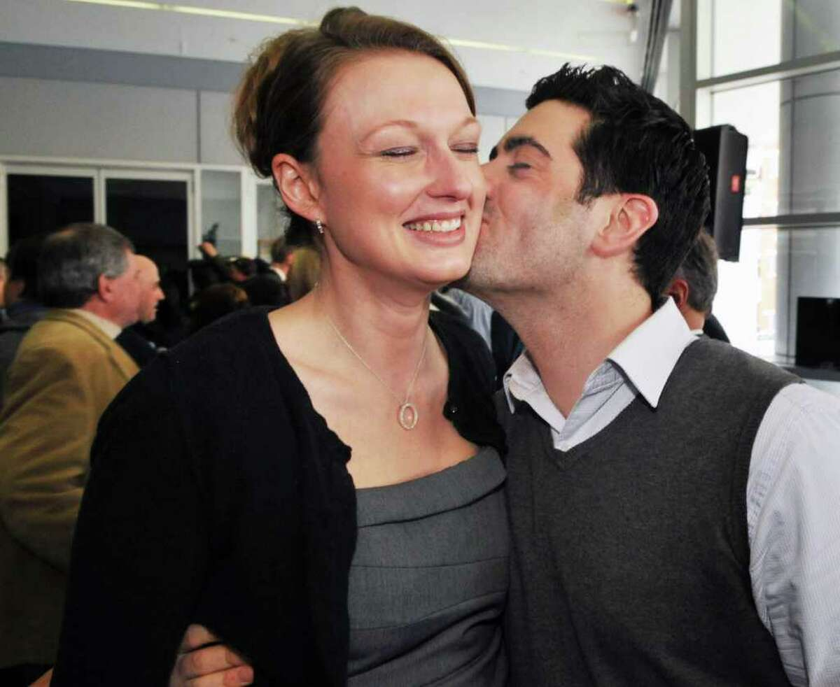 One of seven new lottery millionaires Gabrielle Mahar, left, of Colonie gets a kiss from Boyfriend Scott Conklin of Albany after a news conference at the New York Lottery offices in Schenectady Thursday morning March 31, 2011. The seven winners of the $319 million Mega Millions, are state workers with the NYS Homes and Community Renewal and bought the winning ticket at Coulson's, around the corner from their downtown Albany office. (John Carl D'Annibale / Times Union)