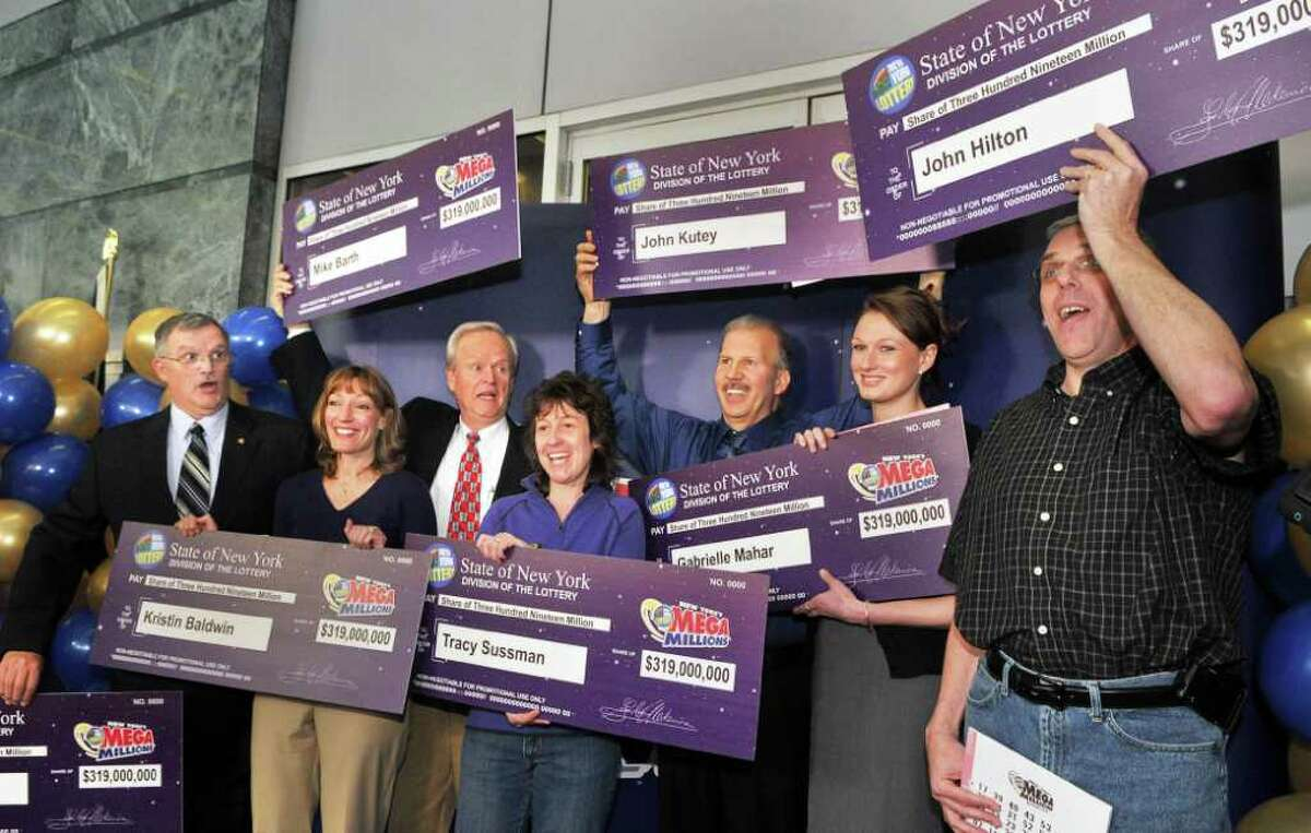 Newest lottery millionaires, from left, Leon Peck of Johnstown, Kristin Baldwin of Clifton Park, Mike Barth of Bethlehem, Tracy Sussman of Colonie, John Kutey of Green Island, Gabrielle Mahar of Colonie and John Hilton of North Greenbush during a news conference at the New York Lottery offices in Schenectady Thursday morning March 31, 2011. The seven winners of the $319 million Mega Millions, are state workers with the NYS Homes and Community Renewal and bought the winning ticket at Coulson's, around the corner from their downtown Albany office. (John Carl D'Annibale / Times Union)
