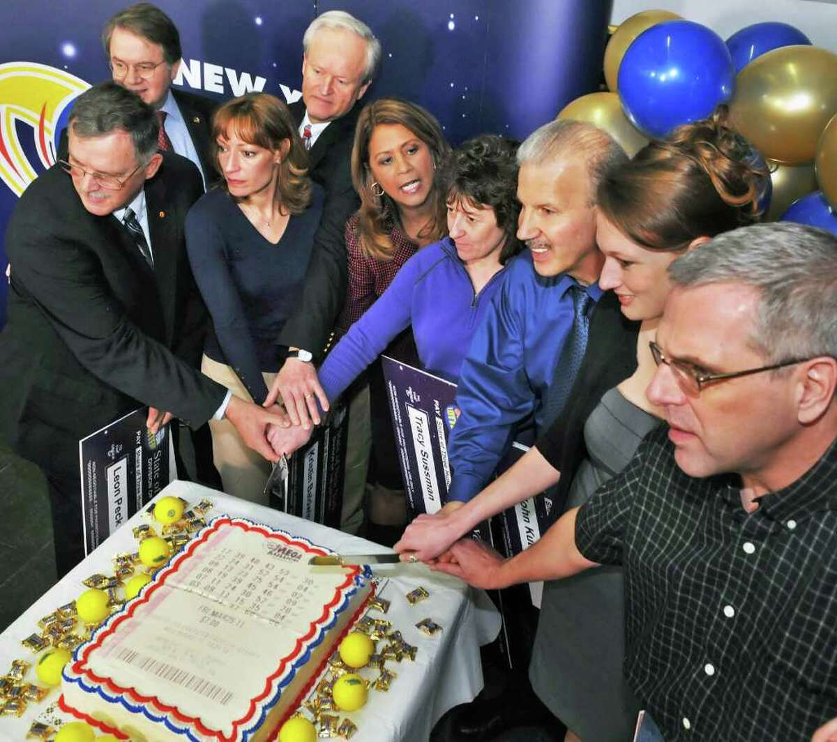 """Posing with a """"Lottery Cake"""" are , from left, Newest lottery millionaires, from left, Leon Peck of Johnstown, N.Y. Lottery Director Gordon Medencia Kristin Baldwin of Clifton Park, Mike Barth of Bethlehem, the Lottery's Yolanda Vega, Tracy Sussman of Colonie, John Kutey of Green Island, Gabrielle Mahar of Colonie and John Hilton of North Greenbush during a news conference at the New York Lottery offices in Schenectady Thursday morning March 31, 2011. The seven winners of the $319 million Mega Millions, are state workers with the NYS Homes and Community Renewal and bought the winning ticket at Coulson's, around the corner from their downtown Albany office. (John Carl D'Annibale / Times Union)"""