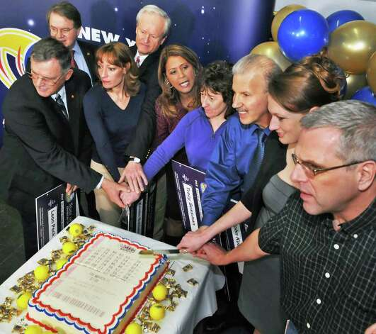 "Posing with a ""Lottery Cake"" are , from left, Newest lottery millionaires, from left, Leon Peck of Johnstown, N.Y. Lottery Director Gordon Medencia Kristin Baldwin of Clifton Park, Mike Barth of Bethlehem, the Lottery's Yolanda Vega, Tracy Sussman of Colonie, John Kutey of Green Island, Gabrielle Mahar of Colonie and John Hilton of North Greenbush during a news conference at the New York Lottery offices in Schenectady Thursday morning March 31, 2011. The seven winners of the $319 million Mega Millions, are state workers with the NYS Homes and Community Renewal and bought the winning ticket at Coulson's, around the corner from their downtown Albany office.   (John Carl D'Annibale / Times Union) Photo: John Carl D'Annibale / 00012588A"