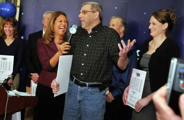 One of seven new lottery millionaires, John Hilton of North Greenbush, center, recounts his experience to the Lottery's Yolanda Vega during a news conference at the New York Lottery offices in Schenectady Thursday morning March 31, 2011. The seven winners of the $319 million Mega Millions, are state workers with the NYS Homes and Community Renewal and bought the winning ticket at Coulson's, around the corner from their downtown Albany office.   (John Carl D'Annibale / Times Union) Photo: John Carl D'Annibale / 00012588A