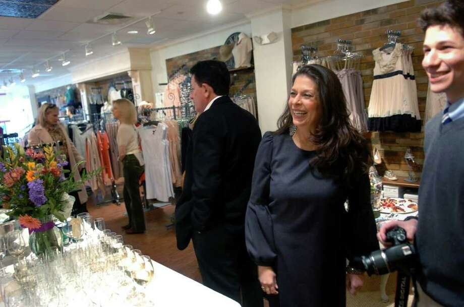 Diane Holz enjoys the grand opening of her new ladies boutique called Apricot Lane, which is located along Post Road near the intersection of Reef Road in downtown Fairfield, Conn. on Thursday March 24, 2011. At right is her son Michael, 16, and her husband Ron, center. Photo: Christian Abraham / Connecticut Post