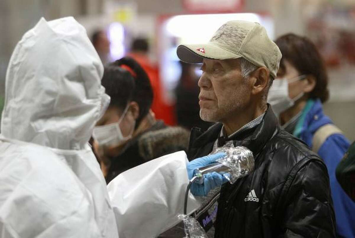 An evacuee is screened for radiation exposure at a testing center Tuesday in Koriyama city, Fukushima prefecture, Japan, after a nuclear power plant on the coast of the prefecture was damaged by Friday's earthquake. (AP Photo/Wally Santana)