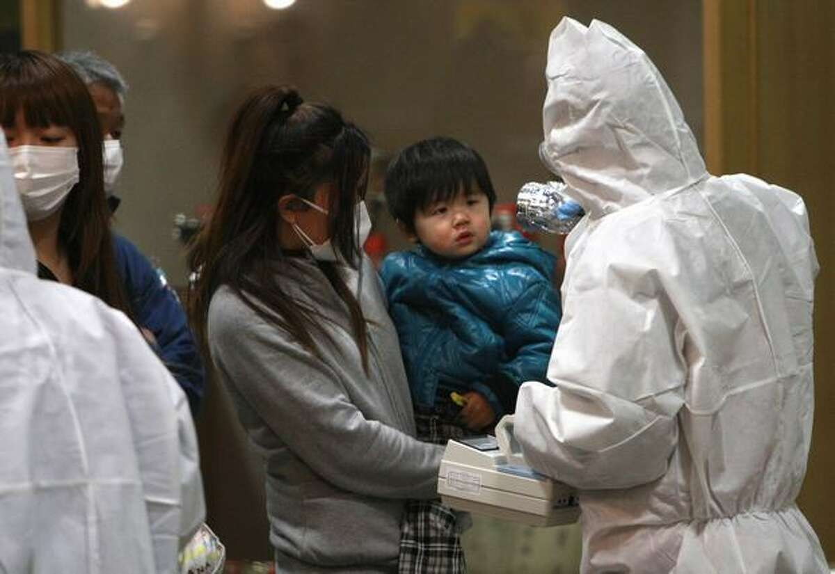 A child is screened for radiation exposure at a testing center Tuesday in Koriyama city, Fukushima Prefecture, Japan, after a nuclear power plant on the coast of the prefecture was damaged by Friday's earthquake. (AP Photo/Wally Santana)
