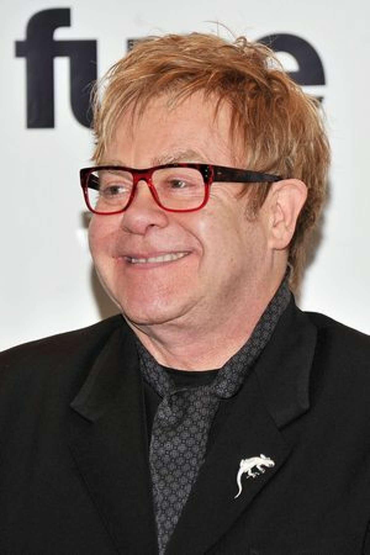 Elton John poses in the press room.