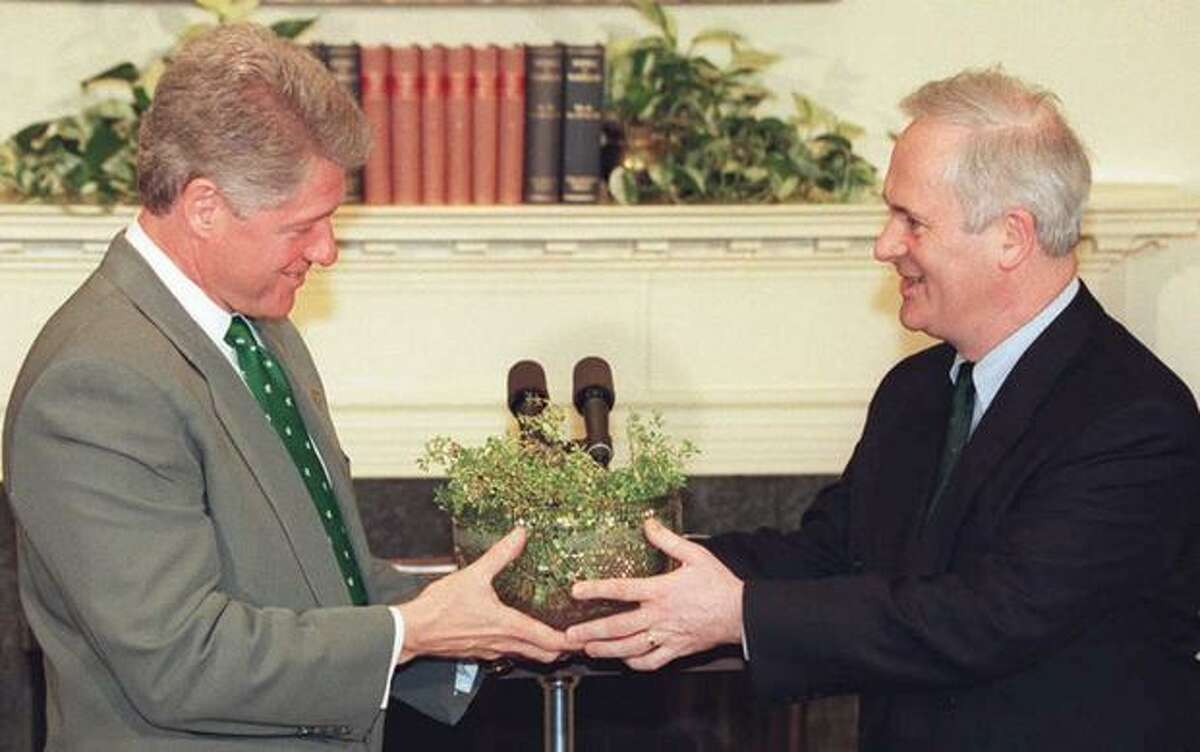 Irish Prime Minister John Bruton (right) presents a bowl of shamrocks to President Bill Clinton on March 17, 1995 in the White House, in Washington, D.C.