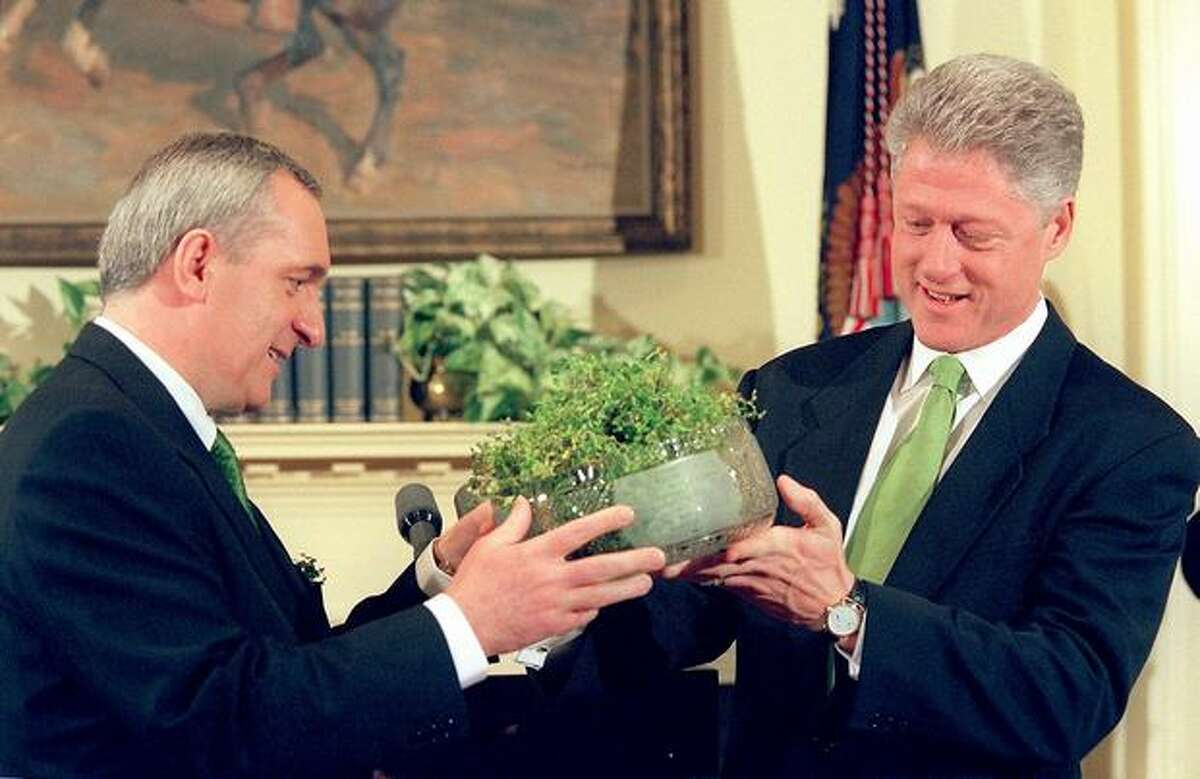 Irish Prime Minister Bertie Ahern (left) presents a bowl of shamrocks to President Bill Clinton on March 17, 1998 in the White House, in Washington, D.C.