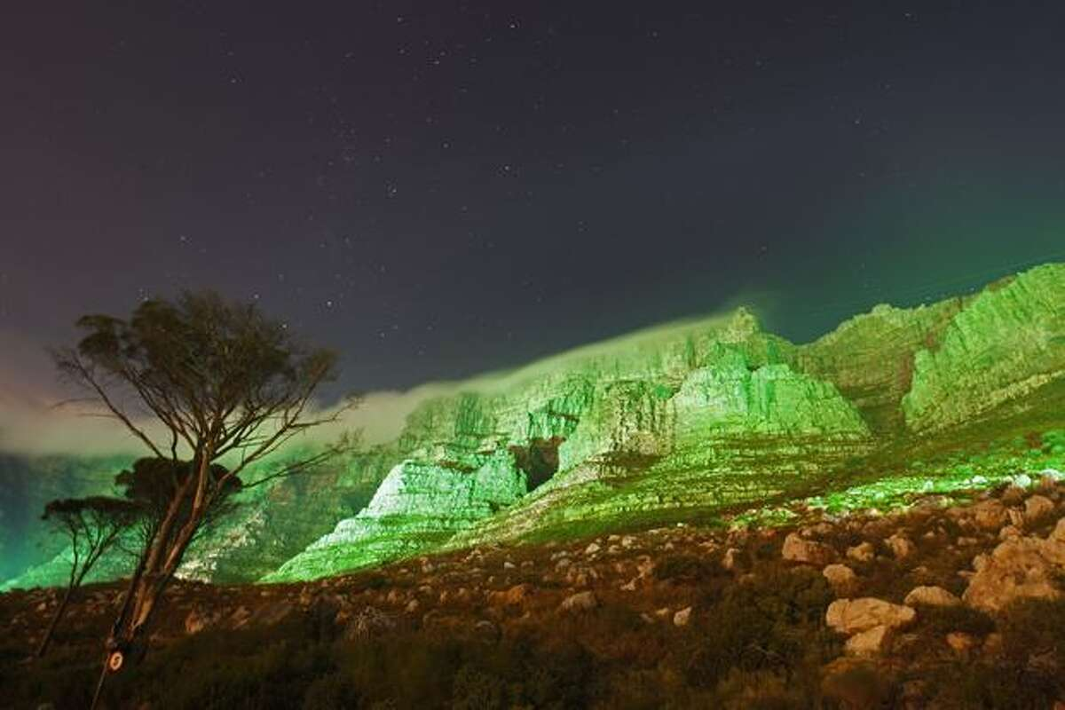 Table mountain is seen lit up in green, in a spectacular display to commemorate St. Patrick's Day in Cape Town, South Africa, Thursday, March 17, 2011. (AP Photo/Schalk van Zuydam)