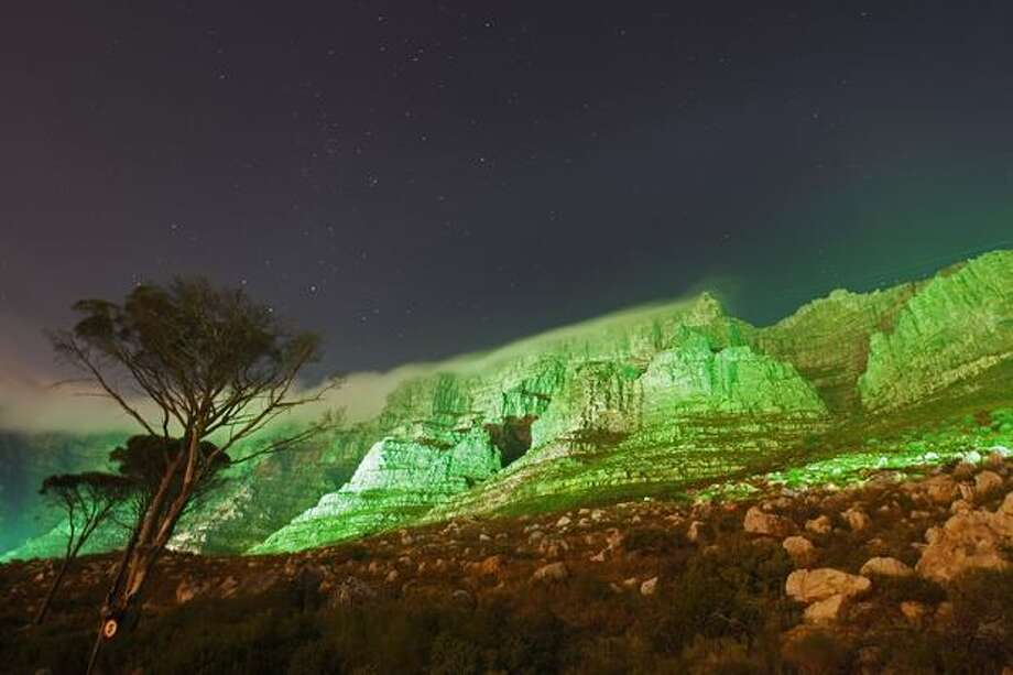 Table mountain is seen lit up in green, in a spectacular display to commemorate St. Patrick's Day in Cape Town, South Africa, Thursday, March 17, 2011. (AP Photo/Schalk van Zuydam) Photo: Associated Press / Associated Press