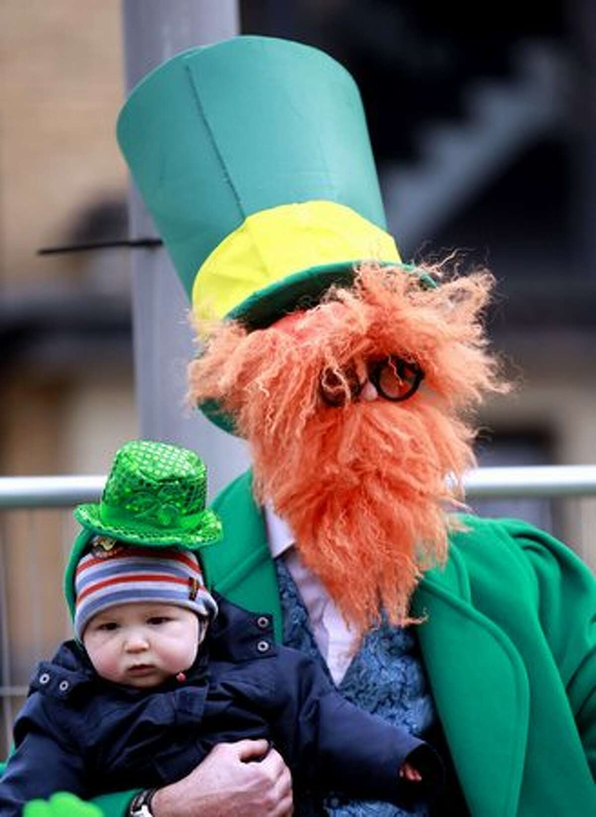 A man and a boy watch the the St. Patrick's Day celebrations in Belfast, Northern Ireland, Thursday, March, 17, 2011. (AP Photo/Peter Morrison)