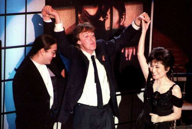 Former Beatle Paul McCartney (C) holds up the hands of the late John Lennon's son Sean Lennon (L) and his wife Yoko Ono (R) after John Lennon was inducted into the Rock and Roll Hall of Fame Jan. 19, 1994. Photo: Getty Images / Getty Images
