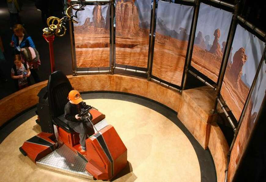 A visitor rides an air chair hovercraft during a preview of the exhibit