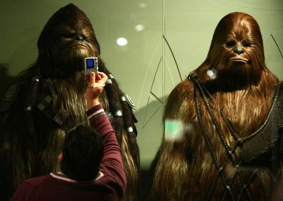 "Costumes for Wookies Tarfful and Salporin are photographed by a visitor during a preview of the exhibit ""Star Wars: Where Science Meets Imagination."" Photo: Joshua Trujillo, Seattlepi.com / seattlepi.com"