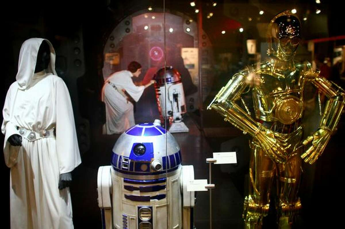 From left, a Princess Leia costume from Episode IV, R2-D2 from Episode III and C-3PO from Episode III are shown during a preview of the exhibit