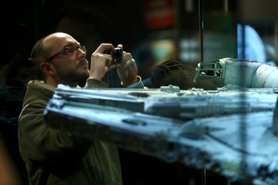 "A visitor takes a photo of the Millennium Falcon during a preview of the exhibit ""Star Wars: Where Science Meets Imagination."" Photo: Joshua Trujillo, Seattlepi.com / seattlepi.com"