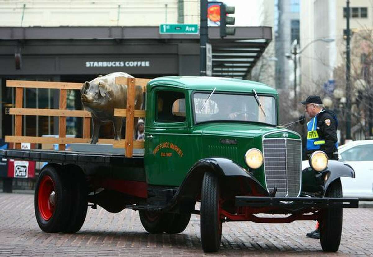 A 1936 International restored by staff at Pike Place Market rolls up to the market with Rachel the bronze pig riding on the back. The bronze cast piggy bank, an icon at Pike Place Market, was recently hit by a taxi and required repair work. On Friday the icon was reinstalled at the market.