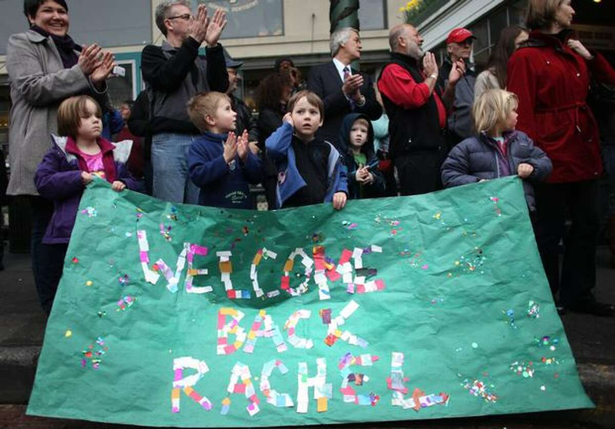Students from the Pike Place Market Child Care and Preschool hold a banner welcoming Rachel the bronze pig back to her corner at the Pike Place Market.