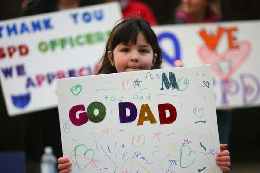 Maddie, 6, holds a sign supporting her dad, a Seattle police officer, during a rally on Tuesday, March 22, 2011 outside the Seattle Police Department's West Precinct in Seattle. The rally was organized to counter recent protests against the department after a number of high-profile incidents where officers were accused of brutality.