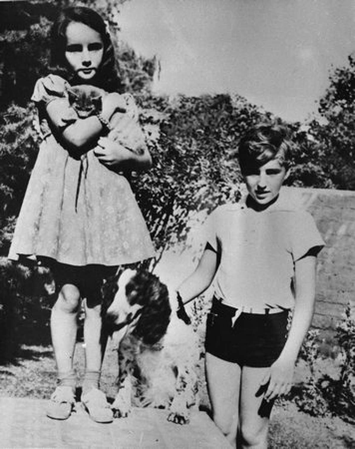Young actress Elizabeth Taylor stands with her brother, Howard, and their pets in a garden, circa 1930's.
