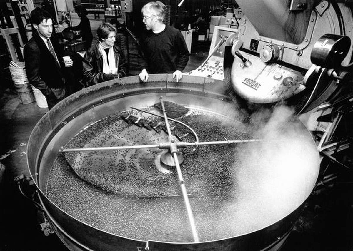 Original caption read: Coffee roaster Jeff Boyd, right, explains the roasting process to Starbucks Coffee shareholders Craig Webster and Judith Caldwell as hot beans pour from the roaster into a cooling vat. The plant is capable of roasting and packaging up to 11 million pounds of coffee annual. Photo from Feb. 1990 by Mike Urban, Seattle P-I