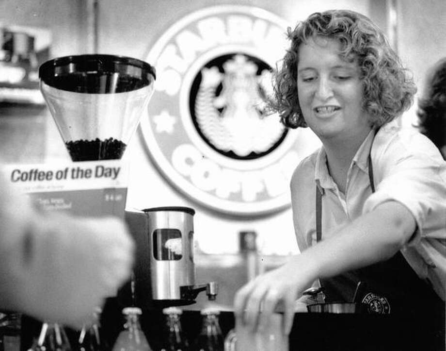 Hanna McElroy, assistant manager of the Starbucks Coffee at 4th Avenue and Spring Street in Seattle, serves a customer. Photo from July 1992 by by Mike Bainter, Seattle P-I Photo: P-I File / P-I File