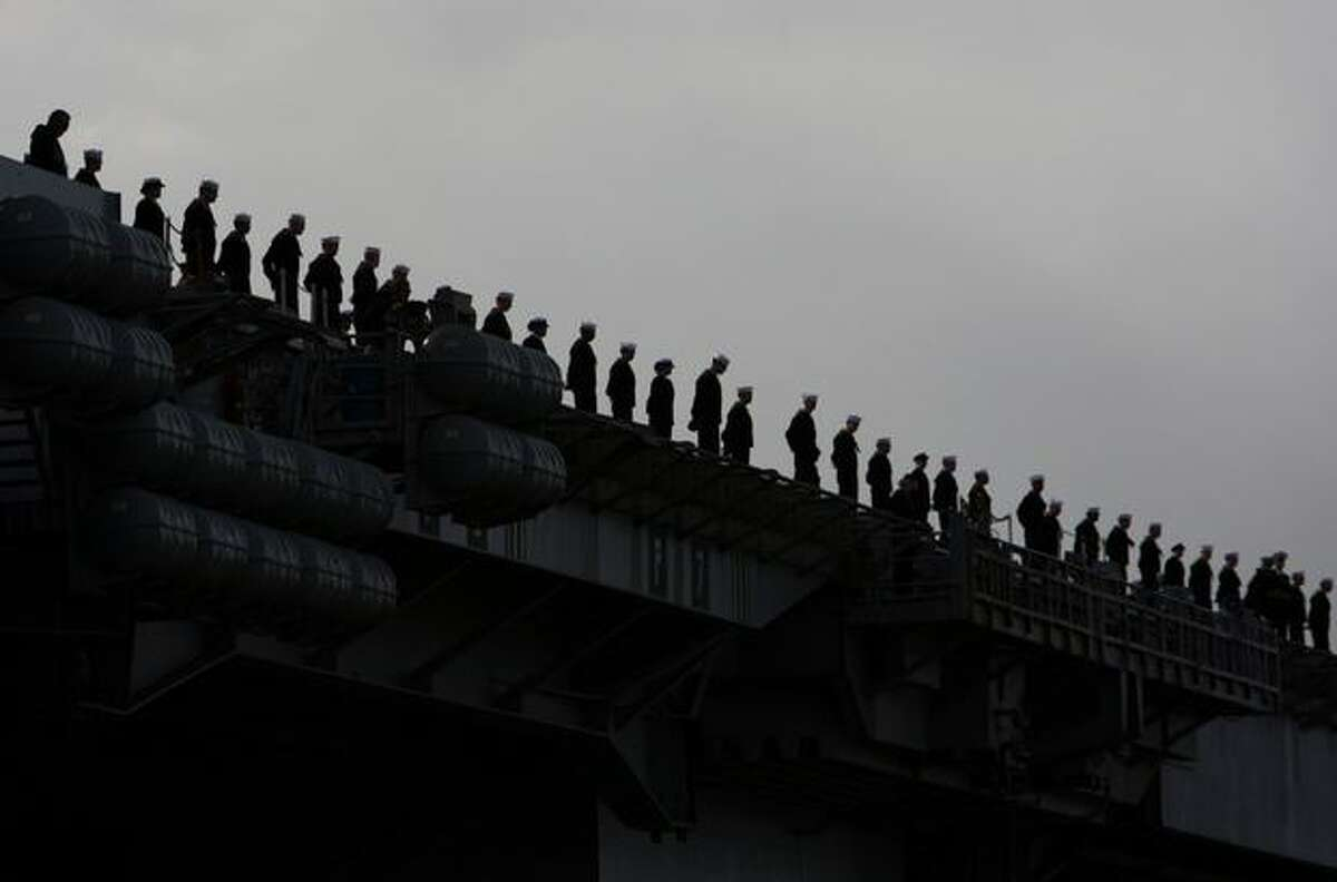Some of the thousands of sailors aboard the U.S.S. Abraham Lincoln line the rails as the aircraft carrier pulls into port.