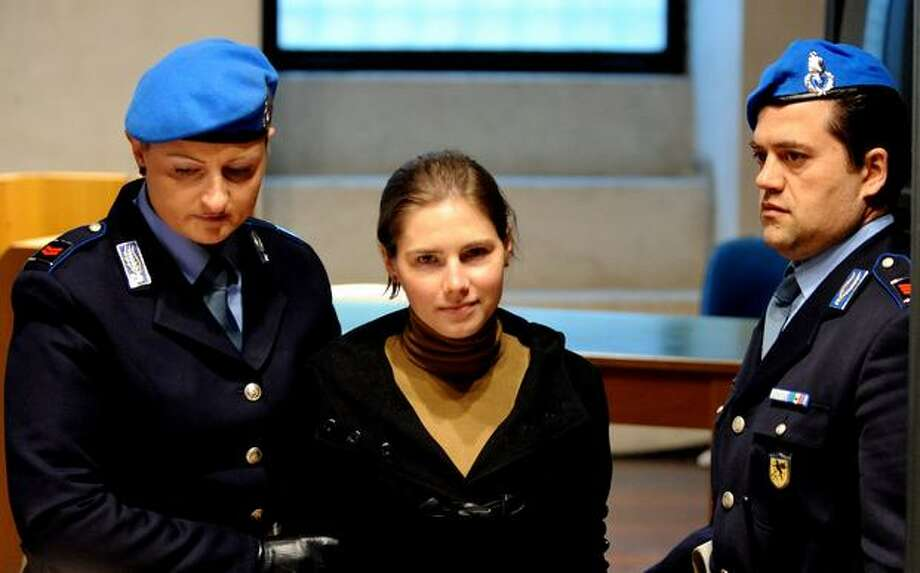 Amanda Knox (C) is escorted by police as she arrives in court before the start of a session of her appeal trial in Perugia, Italy on Saturday, March 26, 2011. Knox was sentenced to 26 years in prison for the 2007 killing of Leeds University student Meredith Kercher, 21, with whom she shared a house in the town of Perugia in central Italy where both were studying. Photo: Getty Images / Getty Images