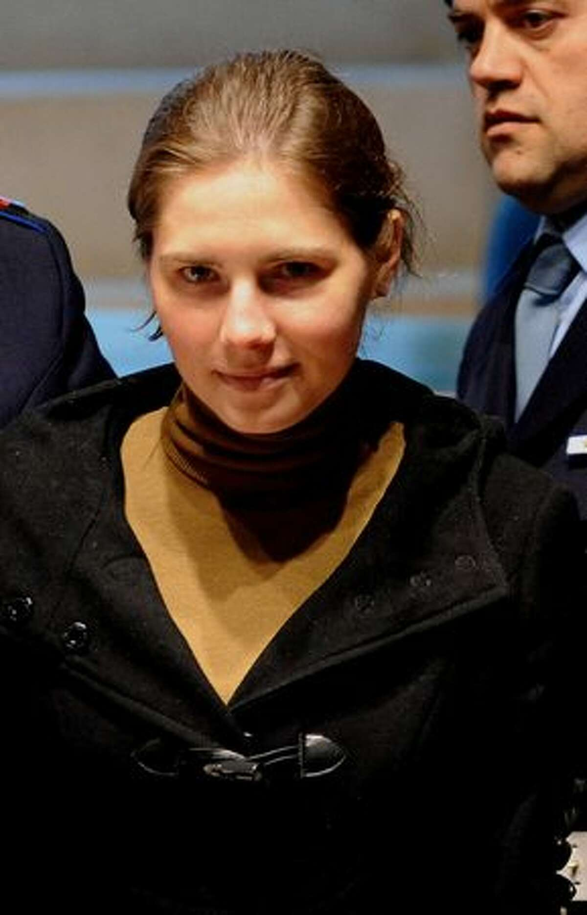 Amanda Knox is escorted by police as she arrives in court.