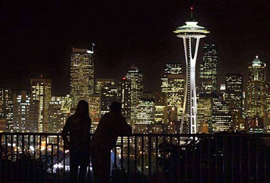 Just after sunset a couple stops to take in the view of Seattle's skyline from Kerry Park on Queen Anne Hill. (Gilbert W. Arias / Seattle P-I)