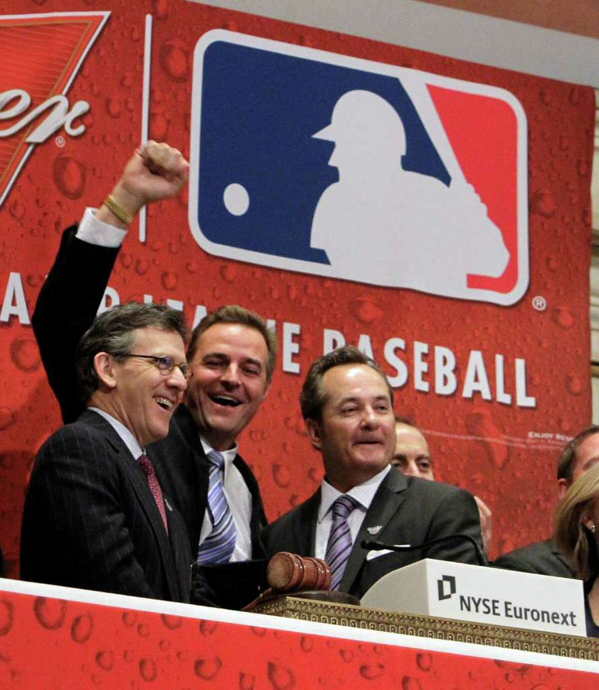 Tim Brosnan, left, with Major League Baseball, former major league pitcher Al Leiter, center, and Mark Wright, with Budweiser, ring the opening bell of the New York Stock Exchange in observance of baseball's opening day, Thursday, March 31, 2011.
