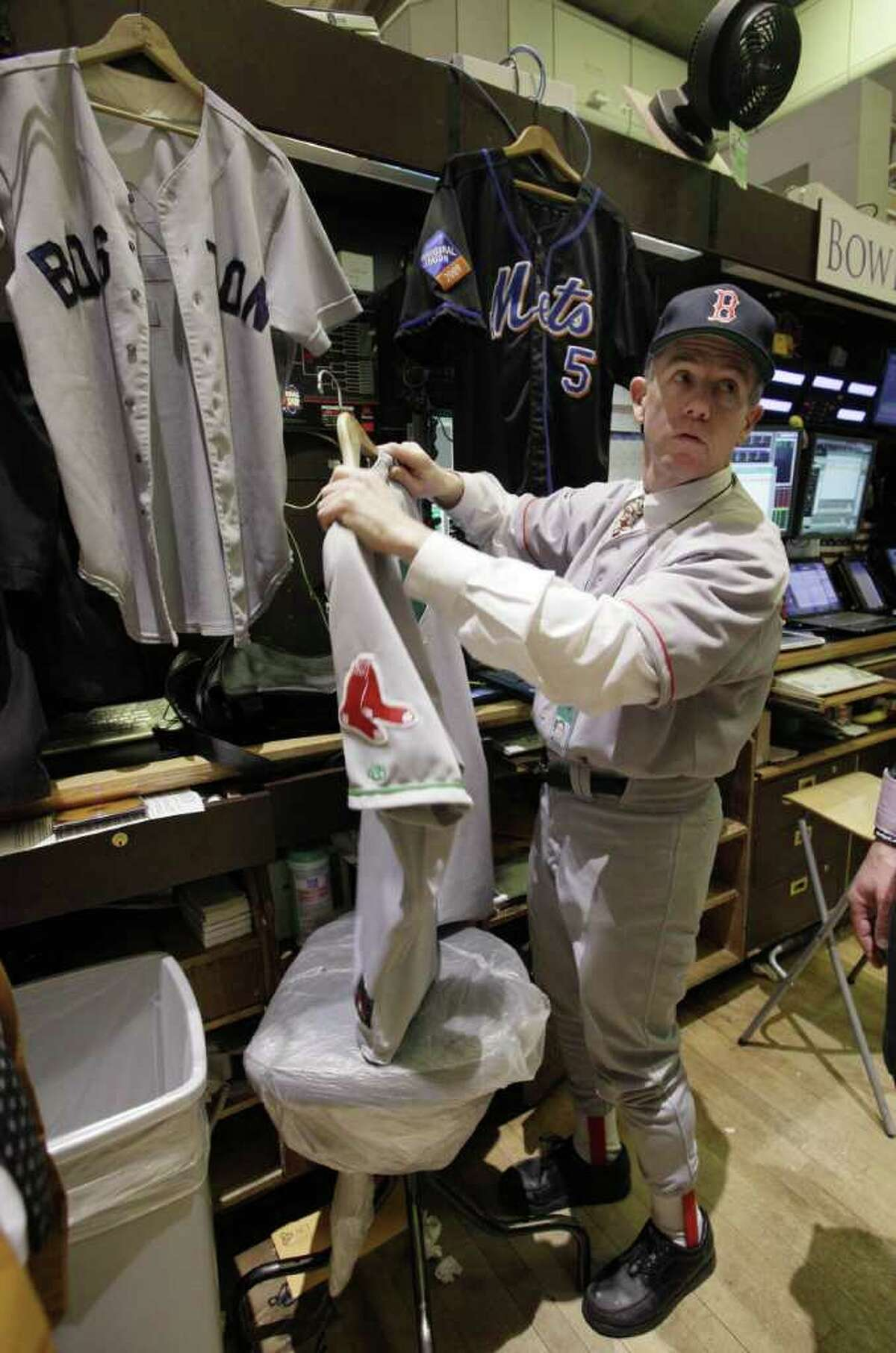 Michael Quinn, with Bowers Securities, is dressed in Boston Red Sox uniform, and sorts through other of his baseball jerseys, as he works on the floor of the New York Stock Exchange, on Major League Baseball's opening day, Thursday, March 31, 2011.