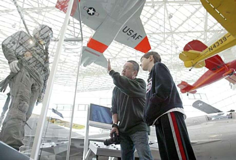 Manuel Loya, 9, listens to his dad Manuel Loya Sr. explains how a flight suit works as the two visit the Museum of Flight. (Scott Eklund / Seattle P-I file photo) / Seattle Post-Intelligencer