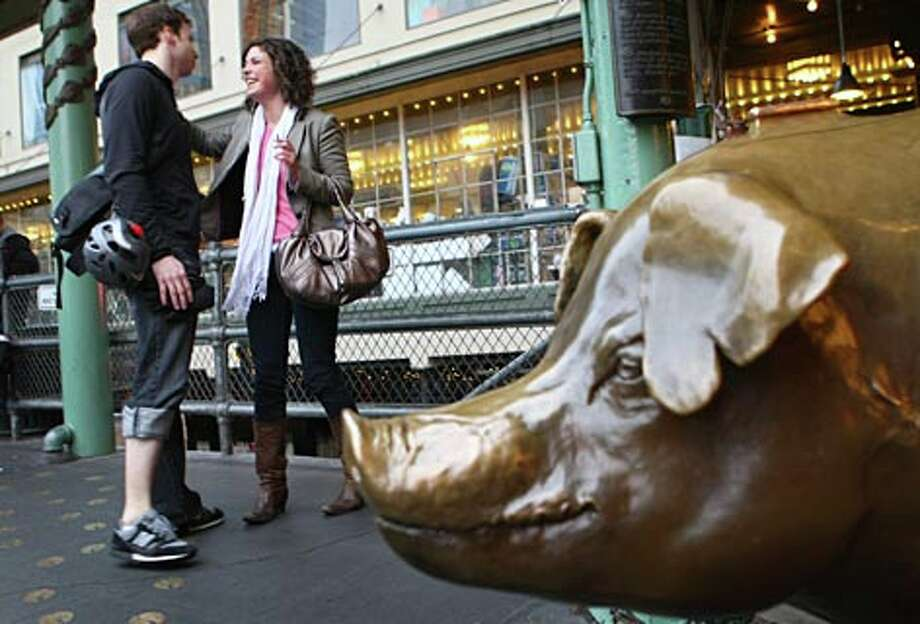 Megan Hartford meets Rick Stockmann in front of the Pike Place Market's signature pig on Tuesday February 26, 2008 in Seattle.  The pig, a local landmark is also known as a meeting place.  Hartford and Stockmann were headed to the nearby Alibi Room. (Josh Trujillo / Seattle P-I)