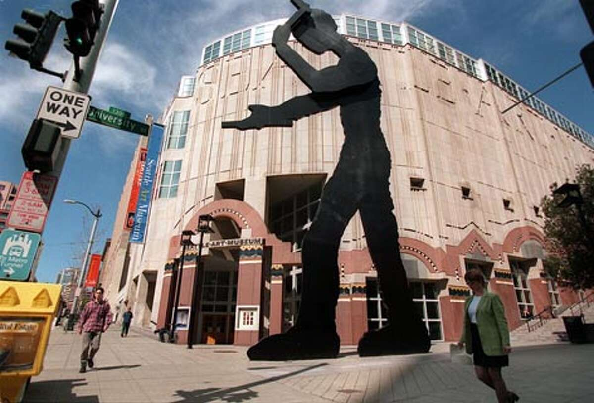 """Art museum opens downtown, 1991: The """"Hammering Man"""" by sculptor Jonathan Borofsky towers in front of the Seattle Art Museum at 100 University St. in downtown Seattle. With the museum's relocation from Capitol Hill, the downtown area began to attract such major arts organizations as the Seattle Symphony, which moved to nearby Benaroya Hall in 1998. (Robin Layton / Seattle P-I file photo)"""