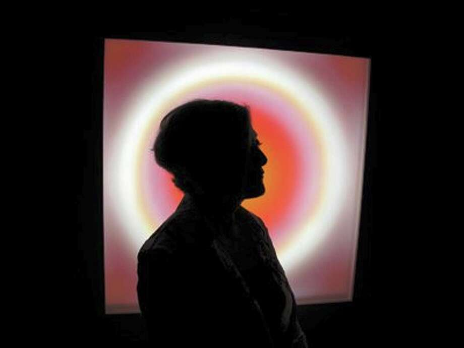 """Cathy Cunningham-Little stands in silhouette in front of her multimedia neon work """"Corona,"""" on view in """"Breathing Light"""" at the Blue Star Contemporary Art Center. COURTESY JOAN FREDERICK"""