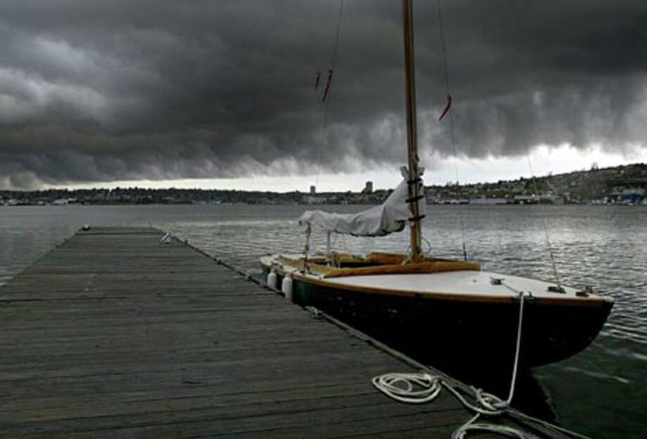 Storm clouds blacken the skies over Lake Union and the Center for Wooden Boats. (Joshua Trujillo / Seattle P-I) / Joshua Trujillo / Seattle Post-Intelligencer