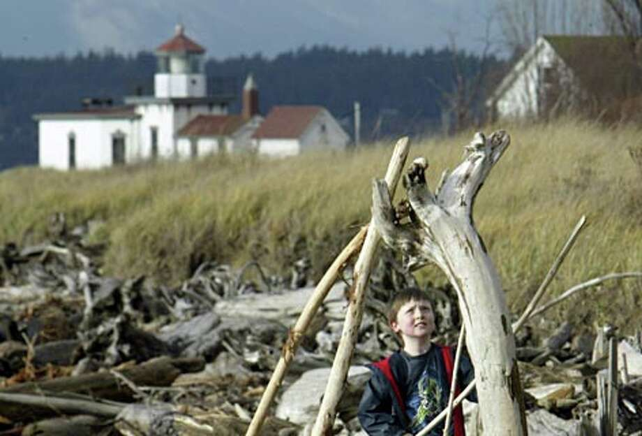 Greg Brewer, 7, of Seattle checks out a driftwood sculpture near the West Point Light Station in Discovery Park. (Andy Rogers / Seattle P-I)