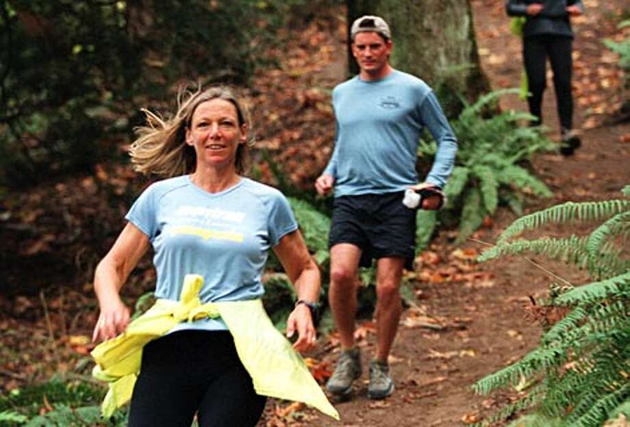 Cruising down a woodsy trail in St. Edward State Park in Juanita is trail runner Cheri Gillis of Woodinville, followed by Charlie Crissman of Seattle and Lorraine Arnold of Woodinville. (Loren Callahan / Seattle P-I file)