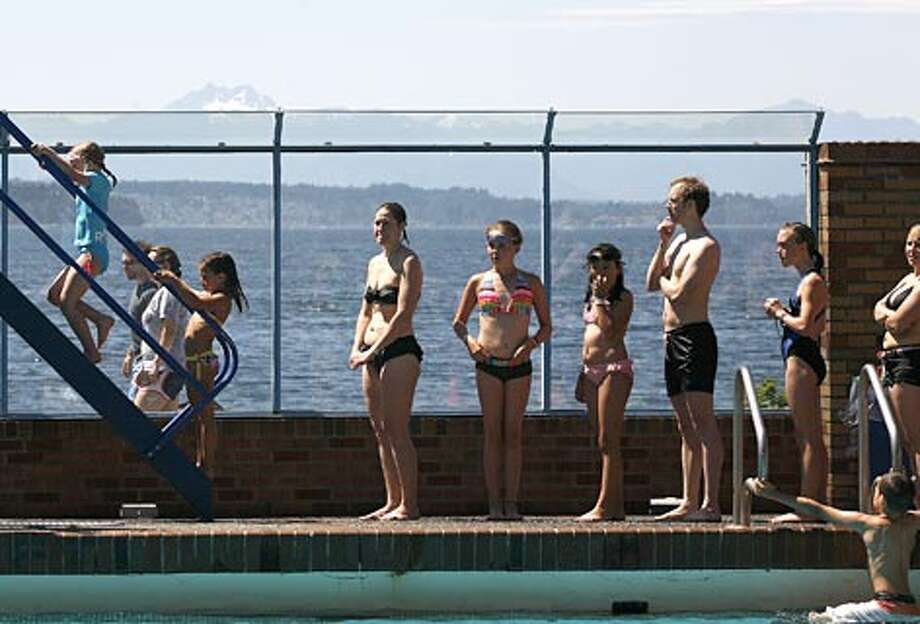 Swimmers wait in line to use the waterslide at Colman pool in Lincoln Park. (Kristine Paulsen / Seattle P-I)