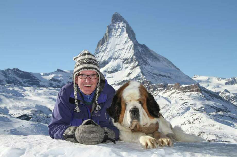 Christopher Kabala, minister of music at Round Hill Community House, poses near the Matterhorn mountain in Switzerland in January. His companion, Mimi, is a St. Bernard, a breed used to rescue distressed travelers in the mountain passes of Switzerland. Photo: Contributed Photo / Greenwich Time Contributed