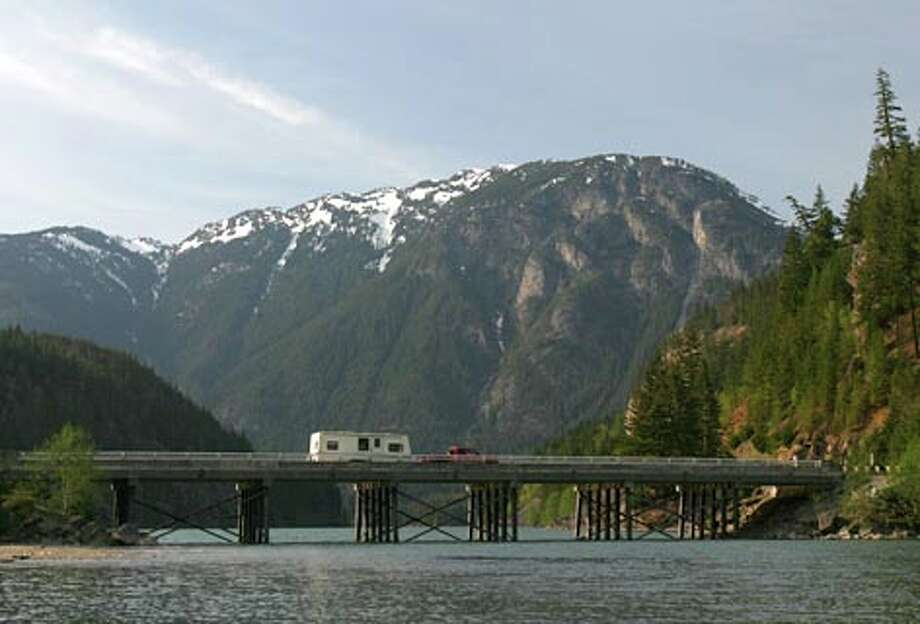 A camper pulled by a truck crosses highway 20 over Ross Lake at Colonial Creek Campground on Friday May 11, 2007 in the North Cascades. (Joshua Trujillo / Seattle P-I) / Seattle Post-Intelligencer