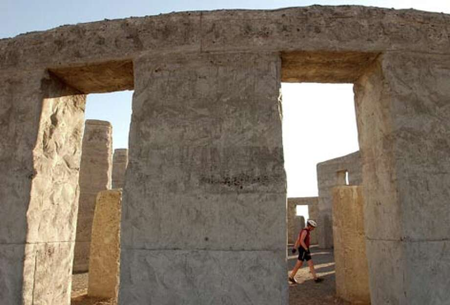 A bicyclist wanders through the Stonehenge war memorial at Maryhill overlooking the Columbia River and just south of Goldendale Washington. (Jeff Larsen / Seattle P-I)