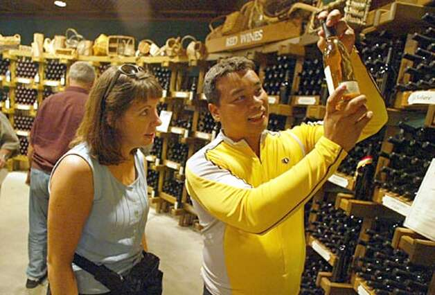 Cyclist Alvin Cruz shows a bottle of wine to Shelley Schaer at the Chateau Ste. Michelle Winery along the Sammamish River Trail near Woodinville on Sunday September 28, 2003.  A popular ride is a trip along the trail and then a stop for lunch at Forecasters restraunt, part of the Red Hook brewery, and stops at nearby wineries. (Joshua Trujillo / Seattle P-I)