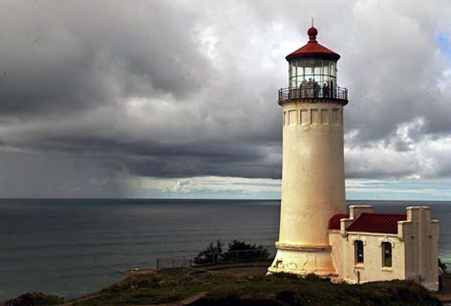 The North Head Lighthouse sits serenely in the park as a Pacific storm rages in the distance. (Jeff Larsen / Seattle P-I)